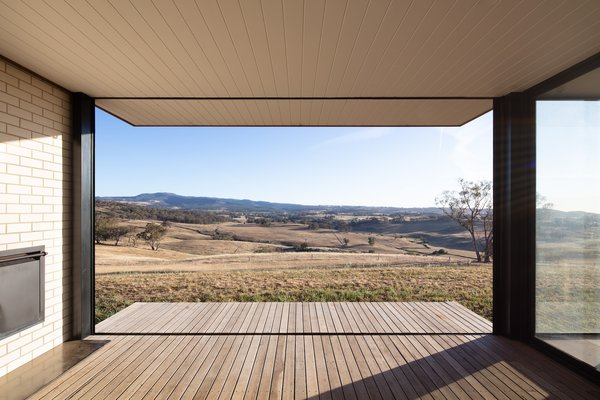 The view from the enclosed porch over the surrounding farmland. Large overhangs provide effective sun shading and protection from inclement weather.