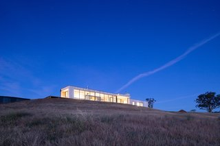 The long, low home sits unobtrusively atop the ridge. Large areas of glazing open the home to the landscape to the south.