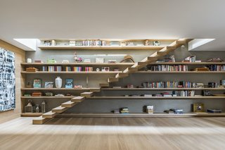 The floating oak staircase in the first-floor family room leads to the rooftop garden, which features a lounge area, grill, and small bar room with a restroom. Bespoke oak shelving behind the stair offers a display area for books and other objects.