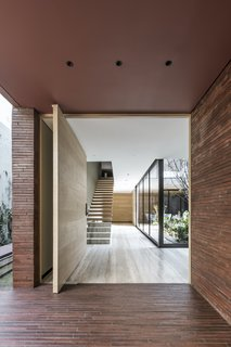 The enormous pivoting front door, which is 2.7 meters high and 2.4 meters wide, is crafted from oak veneer. It opens directly into an expansive view of the internal courtyard garden, creating a delightful moment of surprise and contrast.