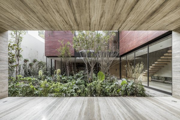 The monolithic brick home in Mexico City by Esrawe Studio looks imposing from the street, but its enormous pivoting door opens to a courtyard that feels like a lush oasis.