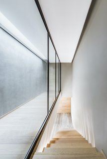 The downstairs hallway flooring is Iranian travertine marble, while the stair and flooring in the upstairs hallway is oak. The walls have been finished with a polished concrete texture.