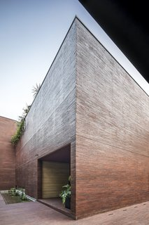 "The entire home is wrapped in a brick ""skin"" that extends onto the ground at the front and sides of the home. The entrance is found through a simple void in the facade beside a pond with floating vegetation that hints at the verdant interior."