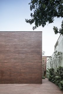 The slim profile of the red bricks used in the facade creates a textured surface across the monolithic form, while red and brown tones of each brick create an organic, varied pattern of color.