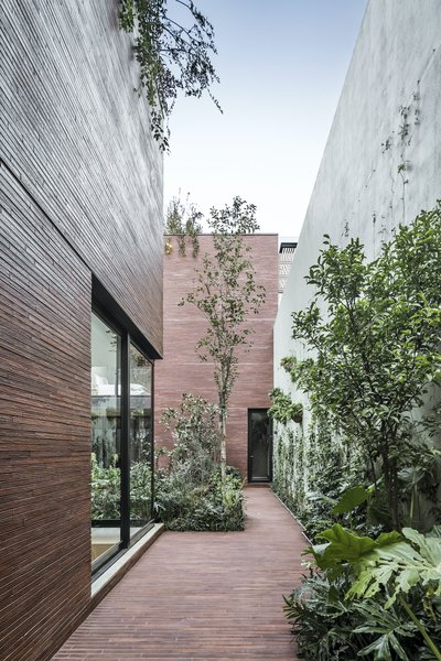 A side patio leads from the front of the home to the courtyard. The same red bricks used for the facade have been used for the paving to create a seamless fabric that wraps the built form and the site.