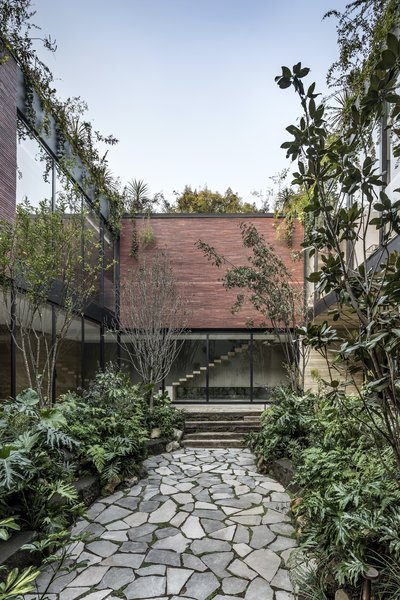 A stone path provides access through the internal courtyard, connecting the various ground floor spaces.