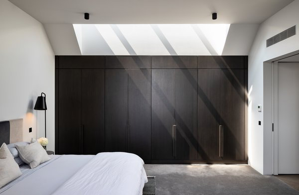 The master bedroom features the same bespoke stained oak veneer joinery as the kitchen. A skylight floods the room with natural light.