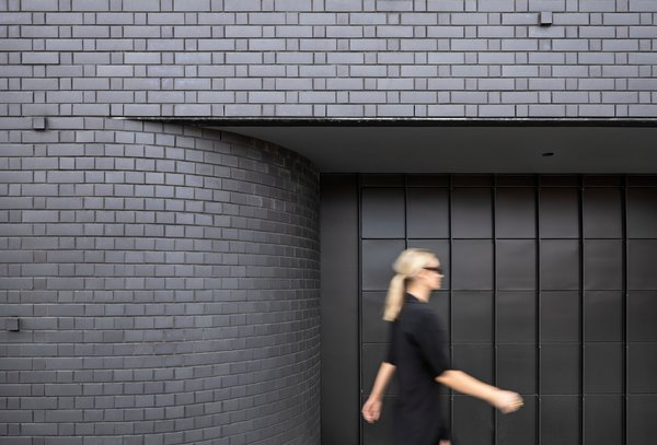 The dark brick facade peels away into the garage, creating an interior stairwell. The garage door, like the front door, is crafted from black steel.