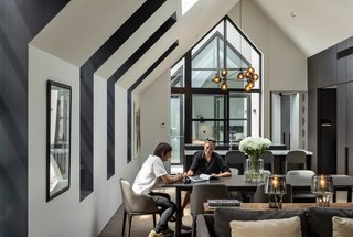 The deep-set dormer windows, which extend into the roof, have black interior surfaces, creating dramatic cut outs in the simple gabled form. The pendant above the kitchen counter is the Modo Chandelier by Roll & Hill.