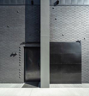 The warehouse-inspired front door on the southern side of the home is crafted from black steel and features a solid steel screen that slides in front of it, creating a completely blank facade.