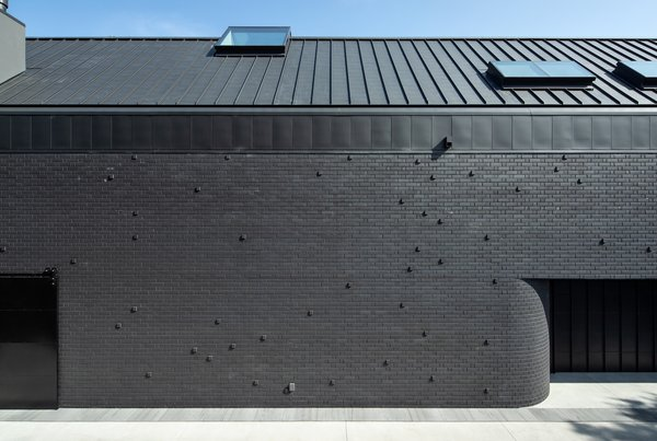 The southern facade of the home—the entrance—is a completely blank facade, which gives the home a private aspect, says the architect. The brick facade curves into the interior of the home.
