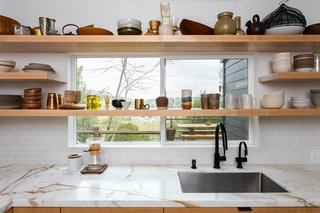 Extending the open shelves across the window in the kitchen maximized the area for storage, creating a visually appealing way to display the couple's collection of ceramic tableware.