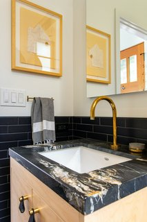 The dark tile used in the guest bathroom was chosen to both complement and create a quiet backdrop for the more expressive character of the marble. Elsewhere, light finishes help to reflect light around the space, making it feel brighter and more open.