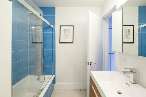 "The downstairs bathroom features blue tiles. As the color orange is used on the main living floor, the color blue is found throughout the basement level. ""It has something to do with the nearby bay and that by going down you are taking a journey under the water,"" explains Edgar."