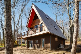To make the home more thermally comfortable and energy efficient, eight inches of insulation was added to the roof, which is finished in yellow cedar shakes—a thicker alternative to shingles. The eaves of the house are painted in Outrageous Orange by Benjamin Moore, referencing the orange elements in the main living space.