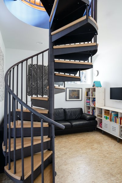 "A spiral stair at the center of the living space leads downstairs to the lower ""basement"" level. The small spiral stair was the only solution for code-compliant vertical circulation in a house with such a small footprint. The alternative would have involved building a ""saddlebag"" onto the side of the house to create a traditional stair run, which would have exceeded the budget."