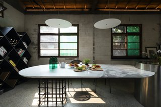 "The marble dining table is supported by repurposed steel rods from the original structure of the building. ""To keep the sense of history and cultural heritage, we didn't want to use only new materials,"" says Chu. ""There is a very interesting relationship between the marble and the steel rods, which is found throughout the home. This balance between old and new is what makes this project so interesting."""