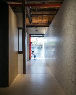 """A six-meter-long white terrazzo wall protrudes from the hallway out past the entrance to form a welcoming gesture that leads people into the home. It not only blurs the boundaries between the interior and exterior, but also separates the public spaces—including the living room and dining/kitchen area—from the private spaces, such as bedrooms and a multipurpose family room. """"We extended a modern gesture, like an arm, that welcomes you in,"""" says Chu. """"It separates the public and private quarters, but also acts as a reflector to bring natural light into the interior."""""""