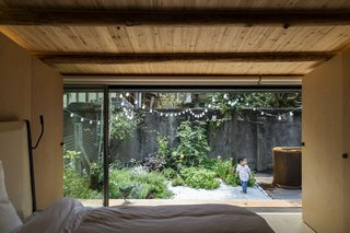 The master bedroom features a fully glazed wall that opens up to the lush courtyard, extending the living space outside. Storage is concealed behind full-height timber doors.
