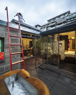 A red ladder, which echoes the vibrant color of the front door, leads to a simple rooftop deck.
