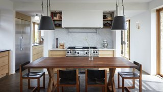 The dining table and chairs in the kitchen were handcrafted by the homeowner from timber harvested on-site.