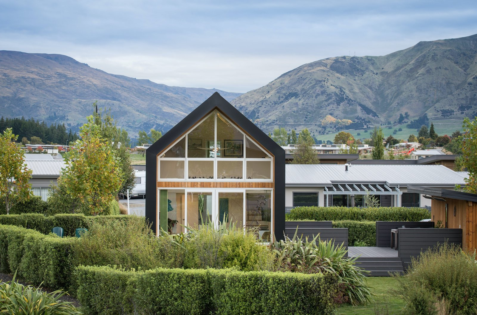 Outdoor, Large Patio, Porch, Deck, Gardens, Trees, Garden, Walkways, Grass, and Shrubs The home opens out to the private garden to the north and remains closed to the road and neighbours on the south side.  Photos from This $155K Tiny House in New Zealand Was Inspired by a Couple's Cycling Tour