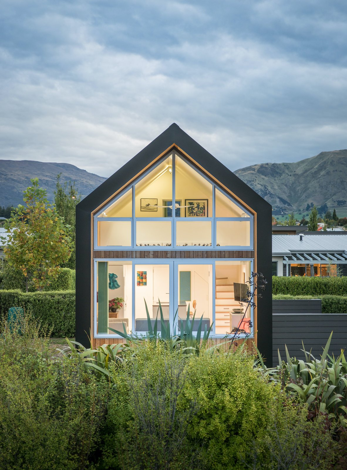 Exterior, House Building Type, Tiny Home Building Type, Gable RoofLine, Wood Siding Material, and Shingles Roof Material The fully glazed north faced overlooks a private garden to the rear. This large area of glazing allows natural light to fill the home.  Dwell's Favorite Photos from This $155K Tiny House in New Zealand Was Inspired by a Couple's Cycling Tour