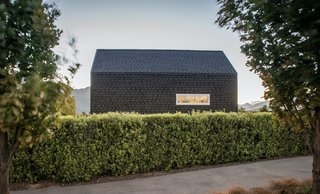 Asphalt shingles wrap around the east facade and onto the roof, allowing the home to be read as a simple, visually unified form.