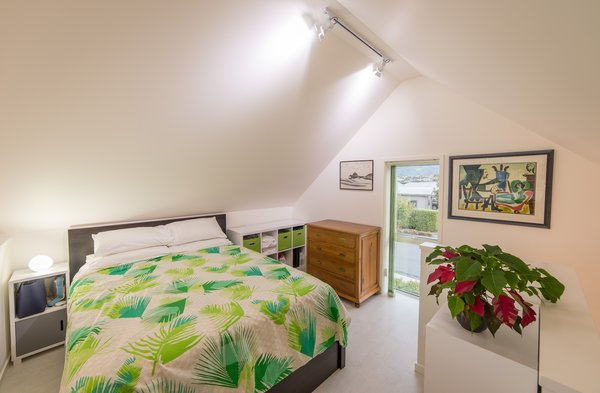 The stairs lead to the bedroom, which is located on a mezzanine in the gable roof space. The bedroom overlooks the living room on one side, while a small window on the other side allows light in while maintaining privacy.