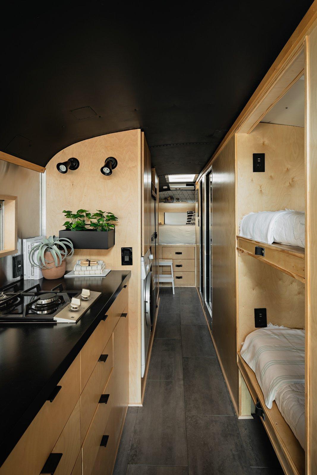 Kitchen and bunks of Scandinavian Skoolie by Killdisco Design.