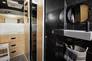 "The build-out was inspired by a ""modern Scandinavian cabin."" Light birch timber contrasts with flat-black elements to allow for a play of natural light in an otherwise dark space. The bathroom sits behind the rear wheels for added headroom in the shower. Five inches were removed from the wheel wells to create additional space in the bathroom."