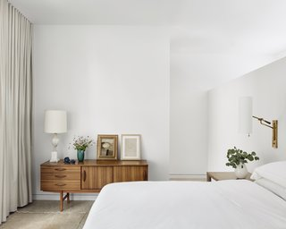 The master bedroom is a calm space with hints of midcentury design inspiration, such as the vintage timber credenza.