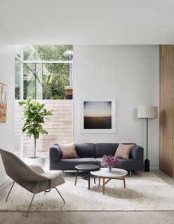 The den offers a second living area and features a sofa from Cassina and a classic Womb chair by Eero Saarinen for Knoll. The artwork is by local photographer Ashley Garmon.
