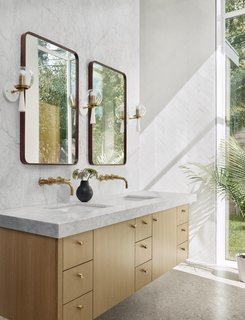 The bentwood mirrors and brass fixtures in the master bathroom fit in with the subtle midcentury design language throughout the home. A large window fills the space with natural light, which bounces off the white Carrara marble vanity top and herringbone tiles on the wall.