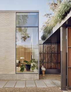 The entrance is through an enclosed courtyard, which features ipe (Brazilian walnut) timber fencing with an exposed painted steel structure topped with planters. The living room is visible through a glazed corner.