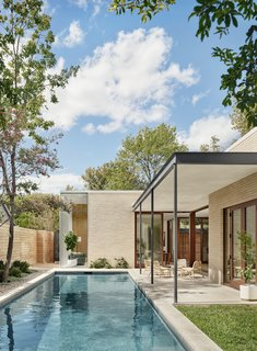 The pool and covered patio sit on the corner opposite of the entrance courtyard. The patio can be accessed through sliding glass doors from both the dining room and kitchen, and the master bedroom. Having lived on the site for so long, designer Jamie Chioco was able to quickly make informed decisions about the design—for example, one of the neighbors uses his backyard for large family gatherings and barbecues, and so it was decided early on to not to have many openings on that facade in order to give both homes privacy.