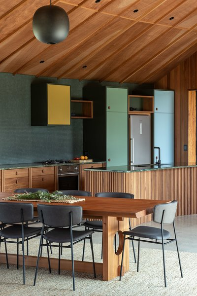 "The colors used in the interior were inspired by the surrounding landscape. The kitchen island is clad in solid timber fluting crafted from durable plantation-grown iroko with with a granite top. ""The green-blue-brown color of the granite benchtops very much reminded me of the colors of the water in the nearby harbor of Tutakaka,"" says architect Belinda George."
