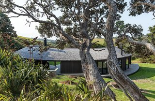 """A shingle roof is """"draped"""" over the curved structure, connecting the interior and covered outdoor spaces. The shingles are crafted from Alaskan yellow cedar, which doesn't require any treatment. The home operates off the grid, so rainwater is collected from the roof for drinking."""