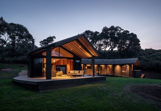 The shingle roof juts out over an ample timber deck adjoining the living area, extending the living space outside.
