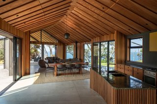 The ceiling is lined in Meranti plywood with cedar battens, and the interior timber walls are tongue-and-groove cedar planking. The Fifties dining chairs are by Italian brand Calligaris.