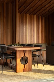 The bespoke dining table was designed by architect Belinda George and crafted using totara timber gifted by the client's brother. It was made by the same furniture maker who was commissioned by the client's mother to make a dining table many decades ago.