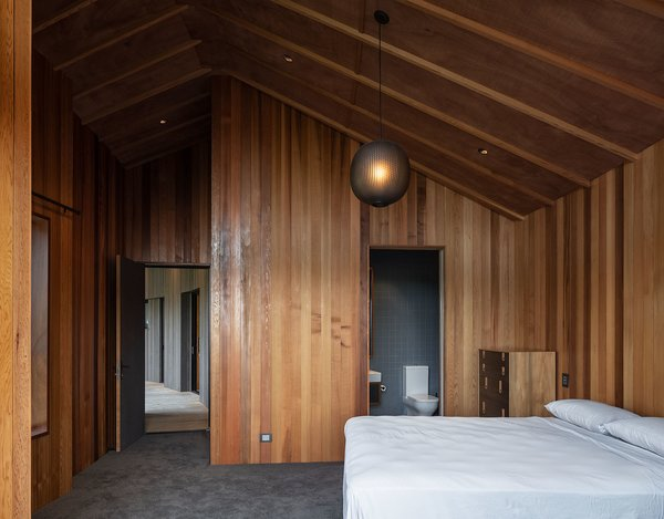 The master bedroom is at the end of the sleeping wing. The elliptical frosted glass pendant lamp was designed by British industrial designer Tim Rundle for New Zealand design brand Resident.