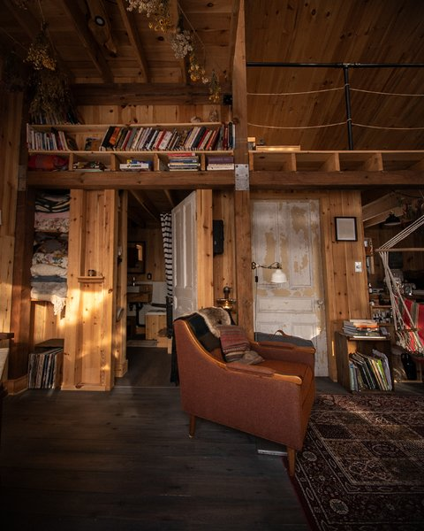 """Built-in shelving in the ground-floor living area provides ample storage for books and records. """"This is my favourite chair, where I like to sit and watch the fire or read a book,"""" says the owner."""