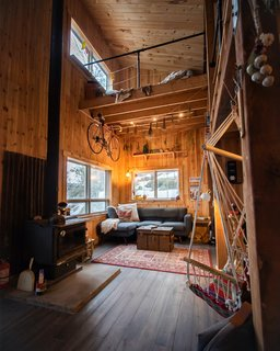 A hammock chair in the living room overlooks the wood stove at the center and the sofa against the west wall, creating a cozy living space.