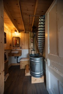 The bathroom features a freestanding tub made from an upcycled feeding trough from a farm, and a salvaged door. There is a composting toilet, and water comes from a 1000-liter rainwater tank located on the second floor.