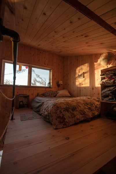 The bedroom is on a mezzanine level at the top of the home, and is accessed via three small steps next to the closet space. There are no curtains on the windows, and the owner wakes up with the first morning light.
