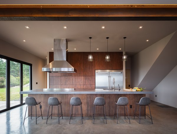 The communal kitchen in the main house provides a space for guests to gather and cook together. This space is sleek and modern with hardware-less marine-grade plywood cabinets and a large, concrete island with seating.