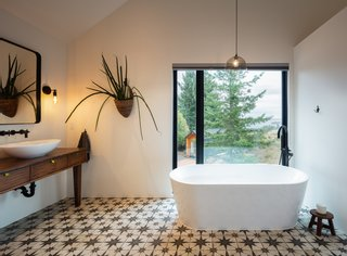 The large master bathroom on the first floor of the main house features a freestanding tub with ocean and forest views.