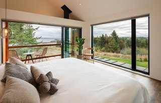 Large, glazed doors and windows on two sides of the master bedroom in the main house bring views of the coastline inside and flood the space with natural light.