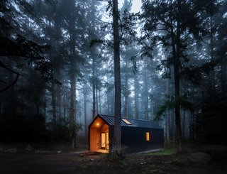 """Five cabins are located in the pine forest surrounding the main house. """"The design for both the main house and cabins at Saltwater Farm resulted from studying traditional Pacific Northwest cabins and refining that vernacular language with one of Scandinavian minimalism,"""" says designer Taylor Bode."""
